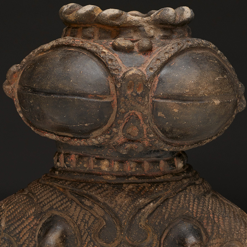 small standing highly stylized figure with very large coffee bean-type eyes; PR lower arm missing; openings at top of head and at bottom; upturned pig-like nostrils; textured body covered with scrolling designs; looping scrolls around stomach/navel and between breasts; small, widely spaced breasts with pronounced nipples; repeating incised zigzags with textured areas on back of head/hair; dark/black patina