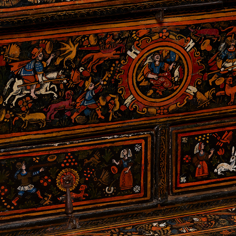 rectangular box with rounded hinged top; hinged front opens to reveal top inner rectangular compartment with two drawers below; exterior, front of drawers and top compartment and front panel decorated overall with brightly colored lacquer imagery--hunting scenes, flowers, couples with various animals (dogs, rabbits, birds); interior of top compartment and cover are rust-colored lacquer; key included