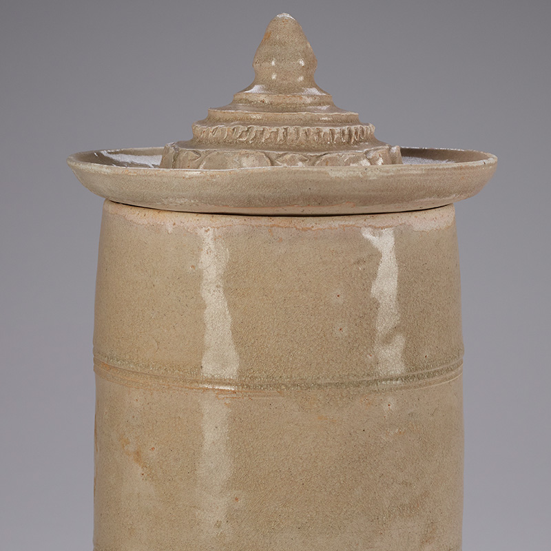 cylindrical container (very slightly flaring outward at center) decorated with applied leaf decorative band at bottom resembling egg and dart patterning; several incised and relief bands around body; wide saucer-shaped conical cover with pointed finial and stepped design, with one step edged in vertical indentations and lowest widest step edged in shorter leaf design; pale greyish glaze overall; white ceramic