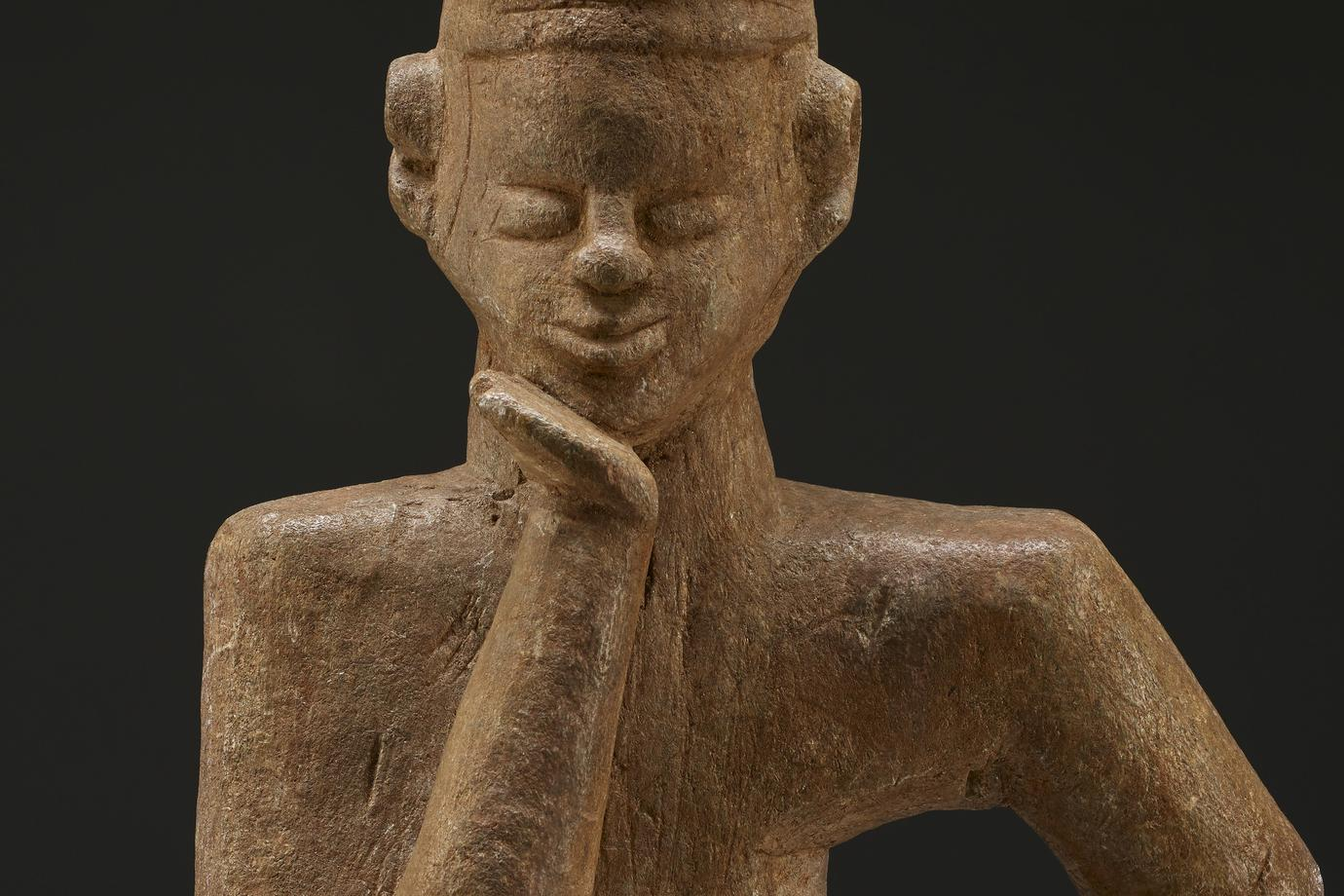 seated figure with legs bent and crossed one on top of the other; PL hand on hip, with elbow bent; very long PR arm with elbow on knee and chin resting on hand; slightly smiling face; large, high-set ears; figure wears a hat with protrusions on top and incised cross-hatched diamonds around edges; stone has tan patina; affixed to bronze-colored metal base