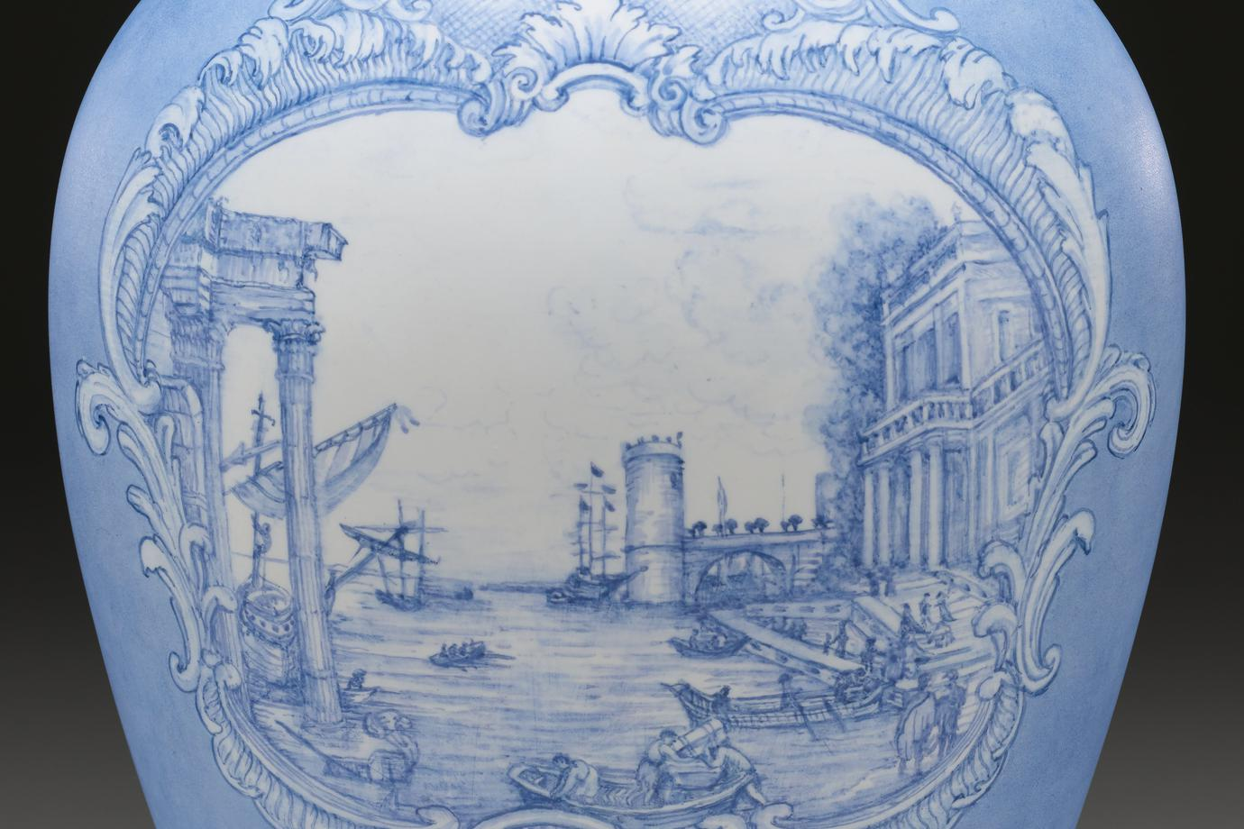 oval concave base; sides flare outward from base particularly on short ends and flare inward toward small oval mouth opening with short neck; white porcelain with light blue designs; wide sides decorated with acanthus-crowned man in jewels and royal robes holding scepters, riding in a small, elegant sailboat with two birds and two fish in cartouche beneath; opposite side decorated with view of row boats at a dock with classical-style buildings and left and right and a round tower at center; partially reclining draped classical figure in cartouche at bottom, with fish and a pair of putti; band of fish around bottom edge; rounded raised cover with knob covered with silver foil