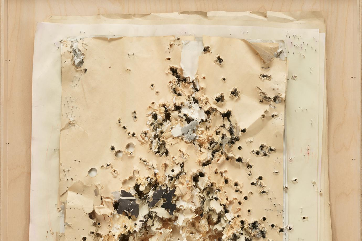 layers of backs of rectangular paper targets of different sizes shot through with bullet holes, with staples sticking out of edges; black and grey on reverse of paper; in plywood shadow box with Plexi cover