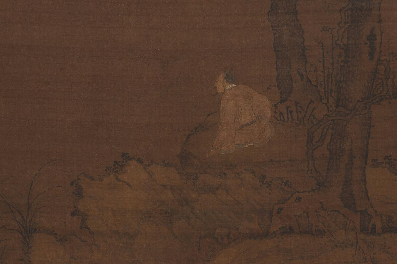 male figure seated below two pine trees on rocky embankment overlooking choppy water, grasses